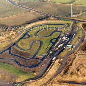 Warden Law Go Kart Track a little more than a mile west of Seaton Village on the site of the former Warden Law Quarry. Site of an Iron Age fort, there are burial mounds nearby.In 995 A.D after years of wandering the north, the carriers of St Cuthbert's coffin came to a halt at a hill called Warden Law, the site of an Iron Age fort near Hetton to the east of Durham. Here the vehicle on which the coffin was transported came to stand still and despite the efforts of the whole congregation of followers who tried to push, the coffin would not move. Aldhun Bishop of Chester-le-Street, the leader of the congregation, committed the monks to three days of fasting and prayer in order to learn the reason why the coffin would not move. After a period of intense meditation their prayers were finally answered when St Cuthbert appeared in a vision to a monk called EADMER. St Cuthbert instructed Eadmer that the coffin should be taken to a place called DUN HOLM. The monks had not heard of Dun Holm, but may have been aware that its name meant HILL ISLAND. Dun was an Anglo-Saxon word meaning `hill', Holm meaning island is a word of Scandinavian origin. Dun Holm was later called DURESME by the Normans and was known in Latin as DUNELM. Over the years the name has been simplified to the modern form - DURHAM.Copyright FlyingFotos  www.seahamfromtheair.co.uk