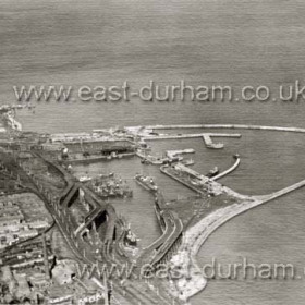 Seaham Dock from the south in the 1930s or 40s.This photograph shows the overhead railroads (staithes) very well. Derelict Bottleworks in foreground.