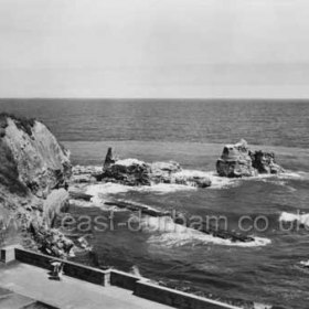 """Looking across the concreted and walled mouth of the dene """"Bessies Hole"""" to the Featherbed Rock, foundations of the old beach railway 1899-1905 still visible c 1960"""