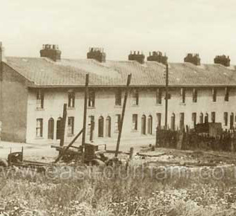 Gallery Row, built around 1850 for bottleworks employees at southern end of bottleworks site, demolished c 1960 . Later the site of Derek Mercer's scrap metal business 1969-99. By the time this photograph was taken, probably 1930s, the gallery (veranda) on the upper storey of this side of the street had been removed.