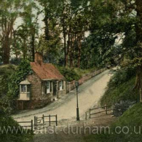 On the banks of the river at Durham c 1910.     The roadway leads down to Prebends Bridge which crosses the river to the Bailey, the heartland of Durham University. The cottage in the picture is still there today.    Caption, Malcolm Fraser