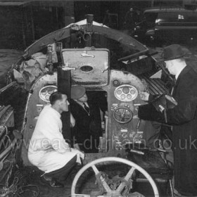 The George Elmy being inspected and examined at Boreham Wood, Herts Depot of the RNLI. Commander R A Gould OBE, RN, Supt- Engineer (wearing overcoat and trilby hat) making examination of lifeboat, 27/11/1962.