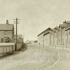 South Hetton, East Front Street. This view is of the Easington to Wardley road (later A182), with what was, after nationalisation of the mines, to become the Colliery Manager's house (South Lodge?) prominent on the left and the Colliery Offices opposite.  The manager's house was subsequently sold to a Surveyor of Customs & Excise and later became a residential home for retired people.  The camera is pointing west-north-westward.  Visible beyond the telegraph pole are the Miners' Institute, the Stationmaster's House and, seemingly blocking the road, Holy Trinity Church.  Caption by Sheldon Clark
