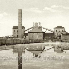 South Hetton Colliery c1930. This picture shows the surface facilities, including at least one Winding House, at a stage well before the redevelopment of the mid-1950s.  It is taken from the Easington to Wardley road (later A182), across the pond which produced thousands of froglets every spring before it was filled in and converted into a car park.  The camera is pointing approximately north-eastward.   Caption by Sheldon Clark