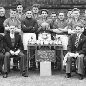 Players and officials of South Hetton Rovers AFC (or possibly South Hetton Colliery Welfare AFC) after the team had won both the Division 2 Championship of the Houghton & District League and the Murton A M Cup in the season 1955/6.  My father, John Sheldon Wesley Clark is seated at the extreme left of the picture, next to a Mr Beresford, I believe.  Although the faces of most of the rest of the officials are familiar, the only other one I can name is Sammy Mitford, who is standing towards the right, wearing an overcoat and scarf.  I think the player standing third from the right was called Whittaker and came from Hetton Downs.  I have no knowledge of the other men's identities.  The shot seems to have been taken at the Colliery Welfare Ground, behind Hawthorn Terrace (as it then was), near where the cricket club now has its clubhouse.                    .Photograph and caption from Sheldon Clark.