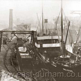 """Londonderry steamship """"Newton"""" unloading pit props in the North Dock around 1900. Lifeboat house built 1870 in left foreground."""