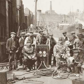 """Divers in North Dock,  c 1915Front row from the left Mr Stanbridge (standing), diver Alf Knapp, diver Mr Beer and  Tommy Phillips ( Trimmer )(standing)Ship behind Mr Beer, Londonderry's """"Newtonards"""""""