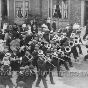 Miners band marching up Marlborough St on Durham Big Meeting Day.  Photograph c 1905??