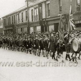Cubs and scouts parade along North Terrace in 1943. Charles Pioli's shop at extreme right.