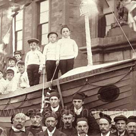Lifeboat ' George and Mary ' made by Coxwain Miller and the lifeboat crew. Londonderry Offices behind, 1911 Coronation celebrations.