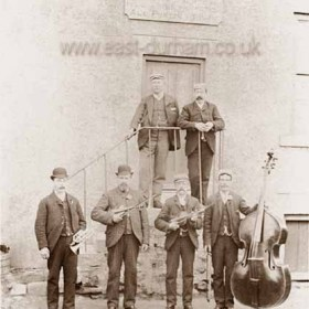 Musicians at the side door of the Dunn Cow Inn, Seaton Village. I would assume that one of the men standing at the top of the steps was John William Tarbitt who was landlord certainly from 1890 to 1902, but I have no records from 1873 to '90 and none from 1902 to '10 (Deborah Bradford has emailed to tell me that her great grandfather John W (Jack) Tarbit is the man standing at top right)