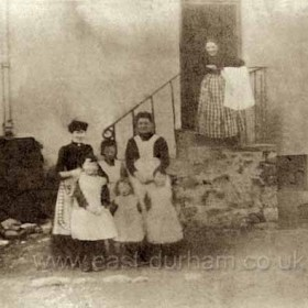 Family and possibly staff at the side door of the Dunn Cow, Seaton Village. Date unknown but probably before 1900.