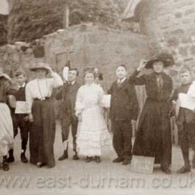 """Seaton Village School c 1920? with stackyard behind. The sign at the teacher's feet says """"Jumble Sale"""""""