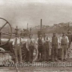 Workmen at Seaham Dock. Steam engine? at left, equipment at right looks like some sort of surveying gear. Possibly blockyard in background. Date not known.