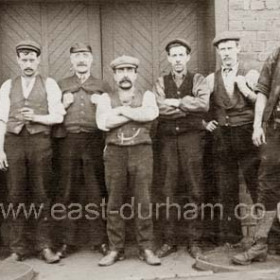 Looks like a colliery photograph, do you know which one, very distinctive doors, have you seen them on another picture?The guy at the right of picture is huge! does he help?